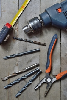Electric drill and tools for working on a wooden surface. view from the top.