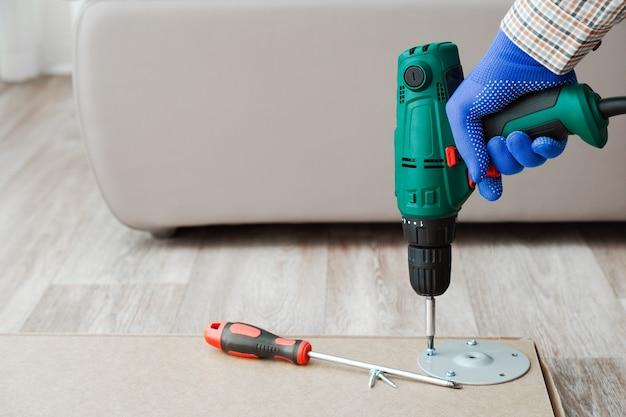 Электродрель работает дома в руках мастера. в процессе сборки мебели мастер собирает столовую мебель с помощью сверлильного инструмента. переезд, обустройство дома, ремонт мебели, ремонт.