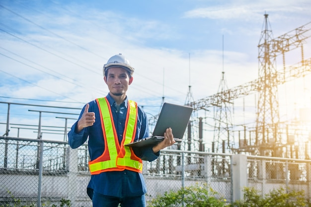 Electric engineer holding computer notebook factory power plant system background