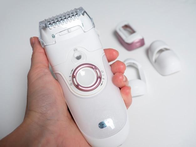 Электрический эпилятор белого цвета в мужской руке на белом фоне. средства для эпиляции, красоты, красоты.