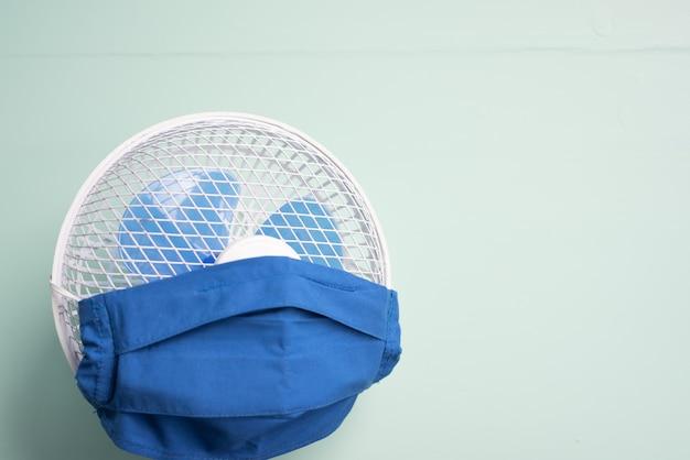 パンデミックの夏のためのdiyフェイスマスクとコピースペースを備えた扇風機