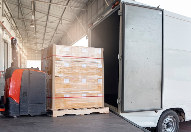 Electric forklift pallet jack loading cargo pallet boxes into cargo truck. shipment, logistics and transportation