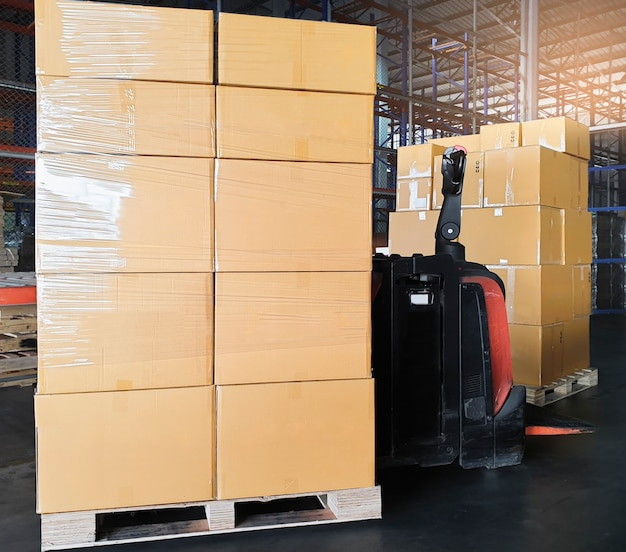 Electric forklift pallet jack with cargo shipment boxes.