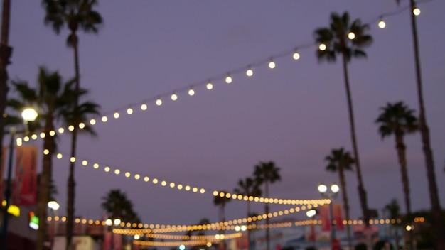 Electric garland, palm trees california usa. beach sunset, coast twilight sky. los angeles lights.