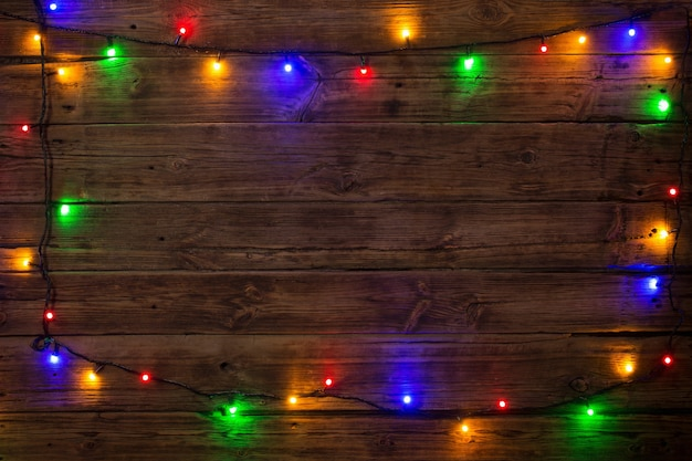 Electric garland with multi-colored light bulbs on a wooden surf