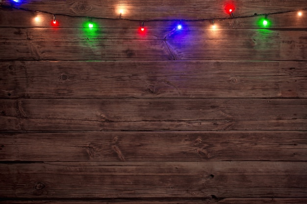 Electric garland with multi-colored light bulbs on a wooden surface, christmas background