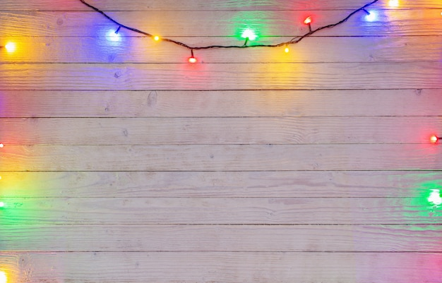 Electric garland with multi-colored light bulbs on a wooden surface, christmas and new year background