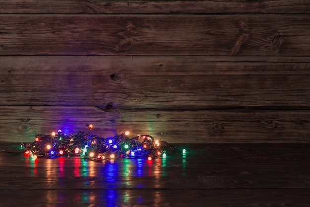 Electric garland with multi-colored light bulbs on a wooden surface