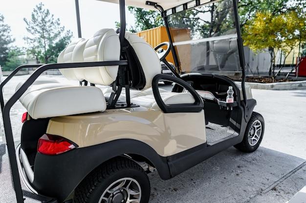 Электромобиль для гольфа припаркован на стоянке возле здания отеля