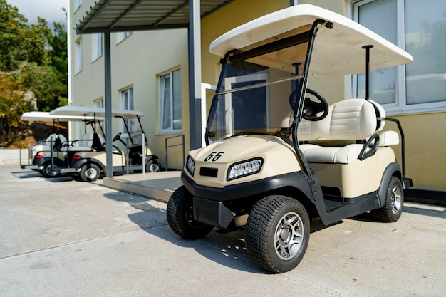 Electric golf car parked on parking near hotel building