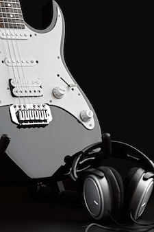 Электрогитара и наушники, никто. струнный музыкальный инструмент, электро звук, электронная музыка, оборудование для сценического концерта