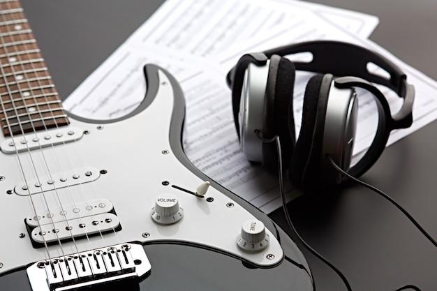 Электрогитара и профессиональные наушники, никто. струнный музыкальный инструмент, электро звук, электронная музыка, оборудование для сценического концерта