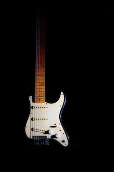 Electric guitar on a black background between light or shadows