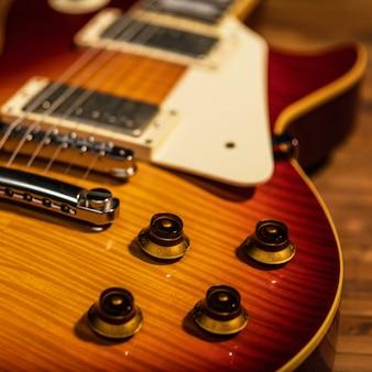 La vista ravvicinata del corpo della chitarra elettrica è sul pavimento di legno