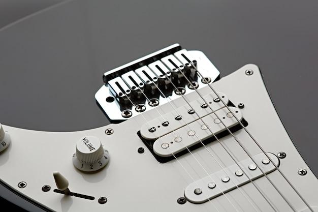 Электрогитара, вид крупным планом на струнах, черный верх, никто. музыкальный инструмент, электро звук, электронная музыка, оборудование для сценического концерта