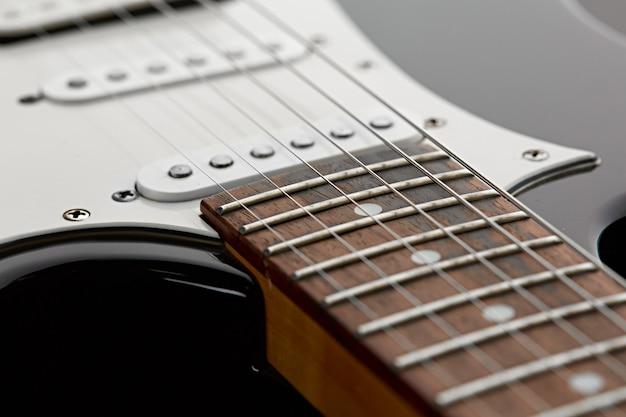 Электрогитара, вид крупным планом на деревянном грифе, никто. струнный музыкальный инструмент, электро звук, электронная музыка, оборудование для сценического концерта