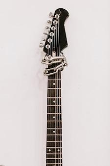 흰 벽에 일렉트릭 기타 fretboard입니다. 음악 장비. 악기.