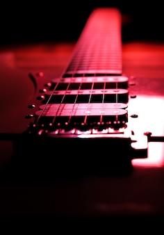 木製の背景にエレキギター。レトロな音楽のコンセプト。赤い影。