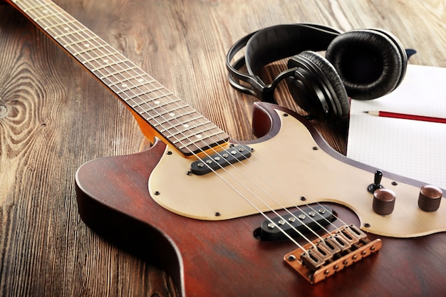 헤드폰 및 노트북 나무 테이블에 일렉트릭 기타