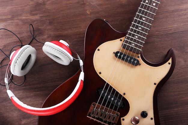 나무 테이블에 헤드폰으로 일렉트릭 기타를 닫습니다.
