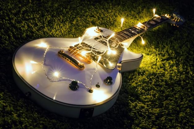 어두운 배경에 불이 켜진 화환이 있는 일렉트릭 기타입니다. 크리스마스 또는 새해를 위한 선물 기타 클래식 모양.
