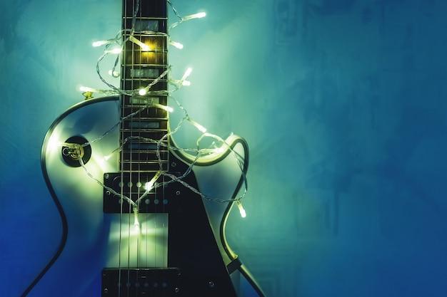 어두운 파란색 배경에 조명 화환이 있는 일렉트릭 기타. 크리스마스 또는 새해를 위한 선물 기타 클래식 모양.
