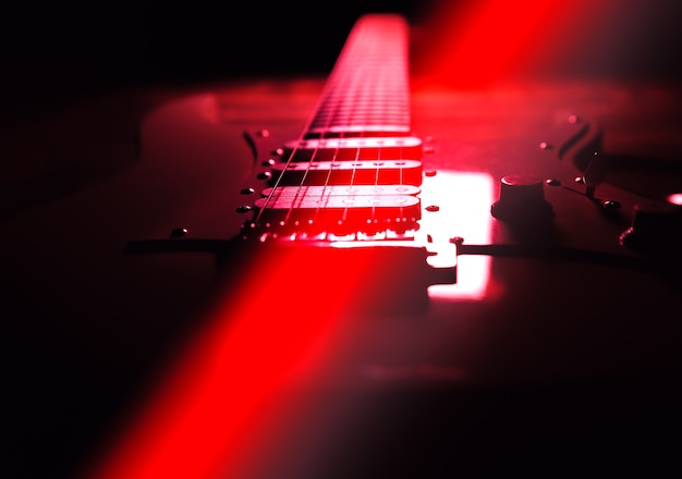 Electric guitar on wooden background. retro music concept. red shadows.