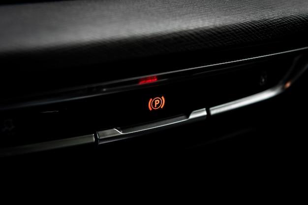 Electric handbrake button of modern car.