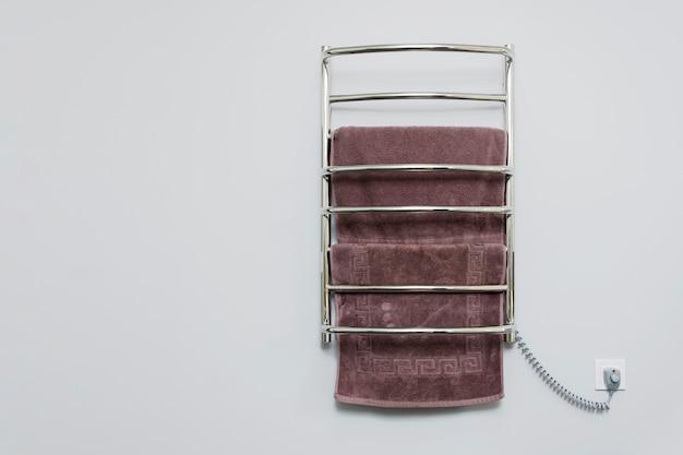 Электрический полотенцесушитель в ванной на фоне серой стены.