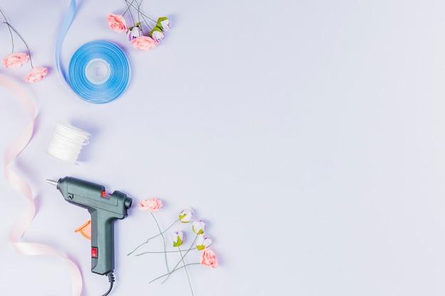 Электрический горячий клеевой пистолет; катушка с ниткой; лента и искусственные розы на белом фоне