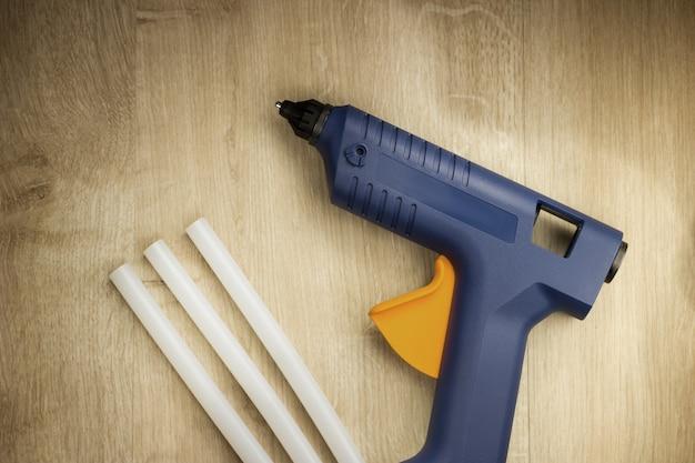Электрический термоклеевой пистолет с силиконовыми палочками на деревянном фоне.