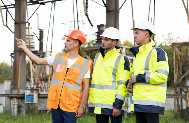 電気産業の電気エネルギー生産コンセプトエネルギー労働者が電力線の近くでの作業について話し合う