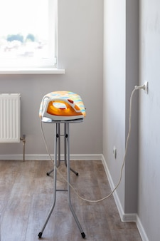 The electric iron is plugged into the socket on the ironing board in the room against the background of the window. iron clothes.