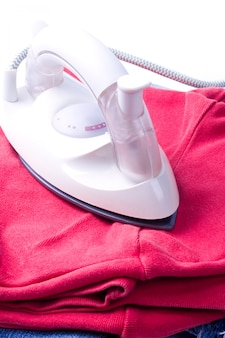 Electric iron and pile of clothes on white background
