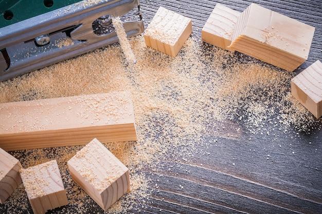 ヴィンテージ木板建設コンセプトの電気ジグソーおがくずと木製レンガ。