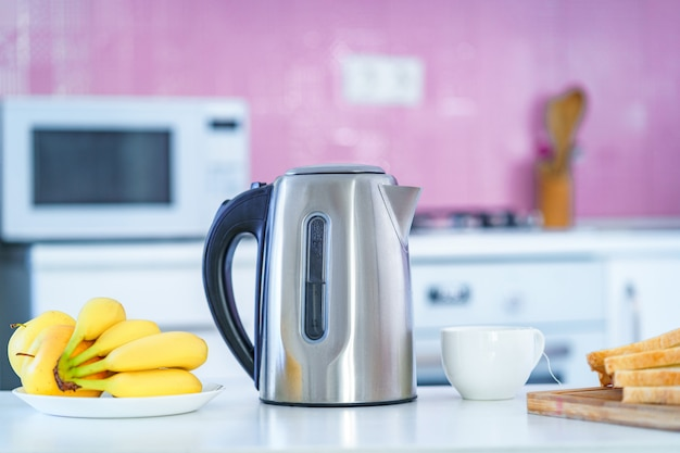 Electric kettle for brewing hot tea for tea time in the kitchen at home