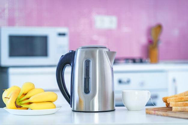 自宅のキッチンでお茶の時間に熱いお茶を醸造するための電気ポット