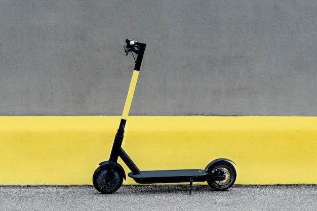 Electric kick scooter against wall. ultimate grey and illuminating.