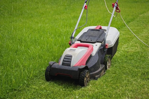 앞마당에 전기 잔디 깎는 기계. 정원에서 잔디 깎는 기계.