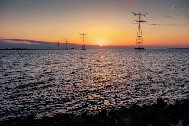 幻想的な日没時の水の上の電線