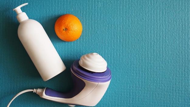 셀룰라이트용 전동 마사지기. 파란색 배경에 로션, 오렌지 및 안티 셀룰라이트 마사지 마사지