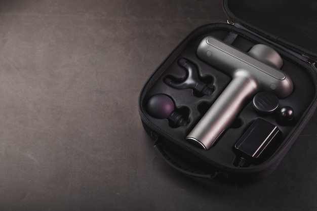 Electric massager machine for body massage in a case on a black background.