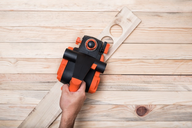 Electric planer in the male hand.