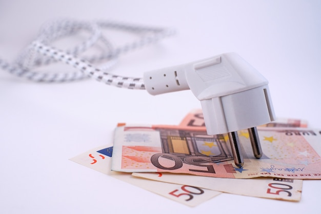 Electric plug on euro banknotes. conceptual image about the rising cost of energy