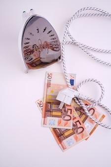 ユーロ紙幣のアイロンの電気プラグ。エネルギーコストの上昇に関する概念イメージ