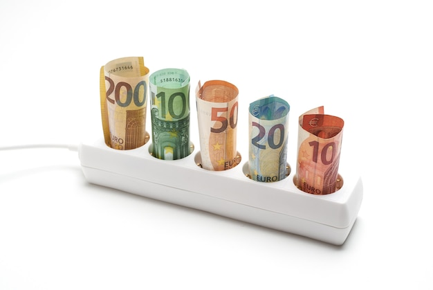 흰색 배경에 지폐가 있는 전기 플러그 스트립, 전기 에너지를 소비하는 개념