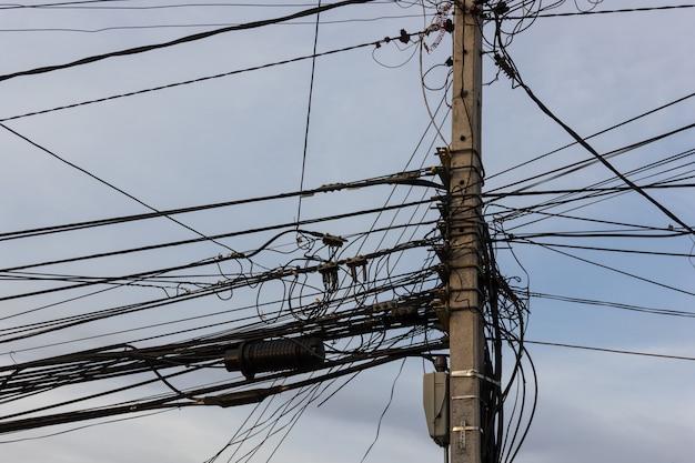 Электрический столб с грязными проводами и кабелями на фоне голубого неба