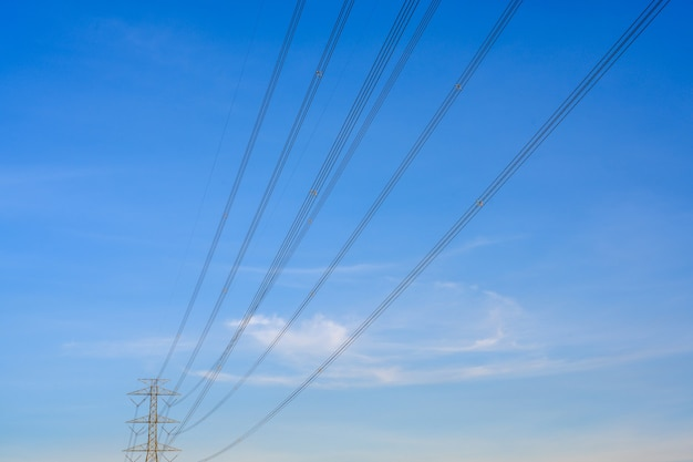 Electric poles and lines at dusk or high voltage towers at beautiful sky.
