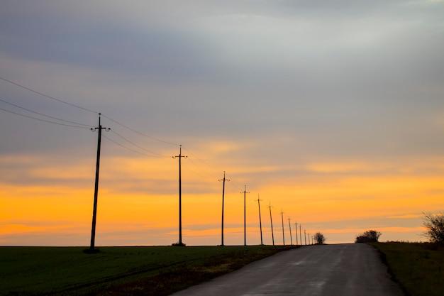 Электрические столбы на проселочной дороге и красивые облака на закате или восходящем солнце