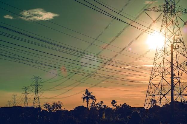 日没の背景にフィールドの電力線プラントステーションタワーポール。抽象的なエネルギー力。